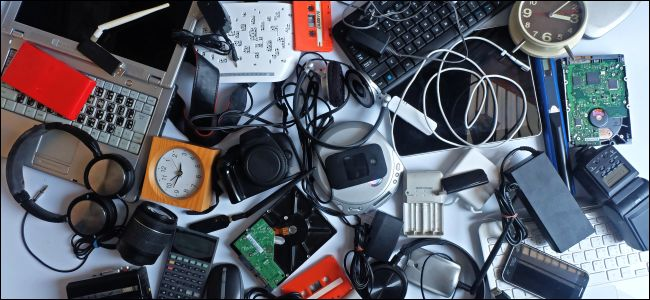 A pile of used electronics including a laptop, headphones, mouse, and keyboard.